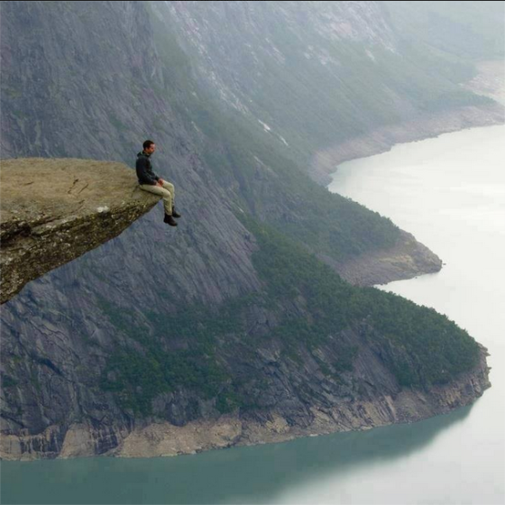 sitting at the edge of a cliff